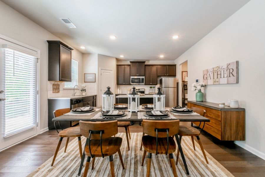 Model home staging in Riverwalk eat-in open concept kitchen with wooden table and six chairs.