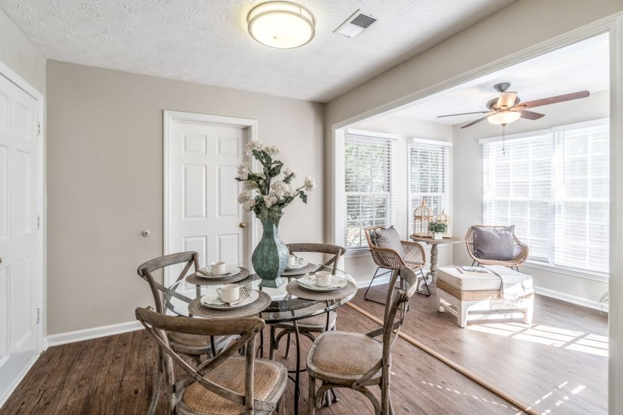 Hampton Square home for sale breakfast area off kitchen with glass round table and four transitional style design chairs. Floral centerpiece is a teal metal vase with magnolia flowers.